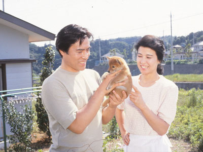 柴犬の子犬のそばで幸せそうに演技をする映画の中の十朱幸代